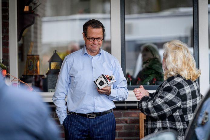 Woonwagenbewoonster Martha Wolters overhandigt wethouder Pieter van Zwanenburg op zijn woonadres in Goor het beeldje van de koe met de gouden horens