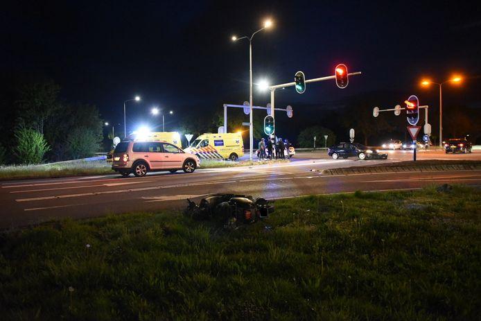 De scooter ligt in het gras, na de botsing met een auto.