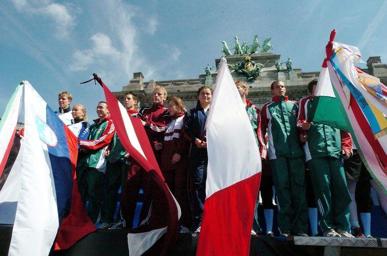 Op de dag van toetreding tot de EU, 1 mei 2004, zwaaien Hongaren in Brussel met de Hongaarse (rechts) en Poolse (tweede van rechts) vlag.  Beeld Hollandse Hoogte / AFP