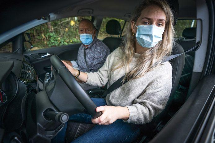 Een rij-instructeur en een leerling dragen een mondkapje tijdens het lessen. Sinds 3 maart examineert het CBR weer.