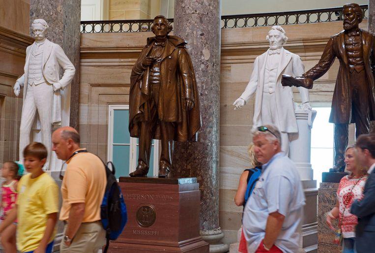 Toeristen lopen in het Capitool langs een van de standbeelden van een leider van de Confederatie: Jefferson Davis (tweede van links). Beeld AFP