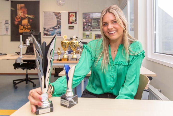 Maud Vlieland met een paar bekers die ze, toen in teamverband, won bij een eerdere debatwedstrijd.