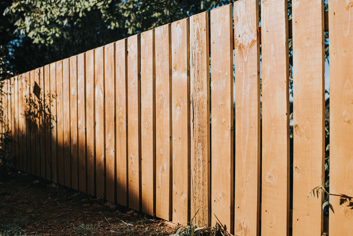 Background image for copy. Textured wooden fence posts, partially in shadow and partially in bright sunlight. Diminishing perspective. Space for copy.