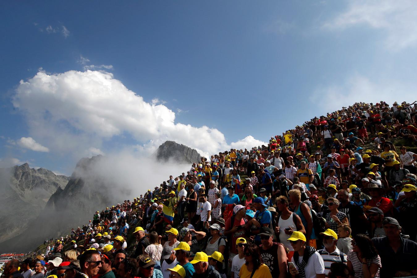 Een massa van wielerliefhebbers probeert bij de Tour de France een glimp op te vangen van de renners.