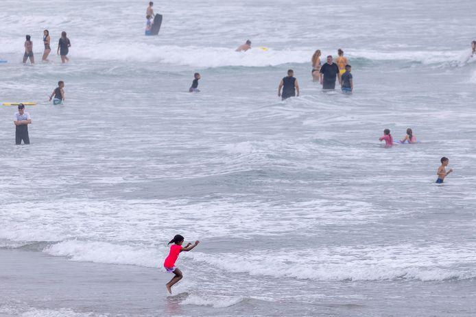 Strandgangers in Oceanside, Californië, zoeken verkoeling in de Stille Oceaan.