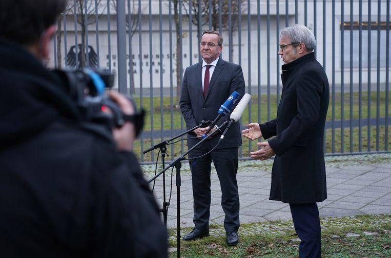 De Duitse minister van binnenlandse zaken Boris Pistorius (midden) en zijn collega Georg Maier van de deelstaat Thüringen geven een persconferentie over corona en de reactie van de protestbeweging Querdenken-711 daarop.  Beeld EPA