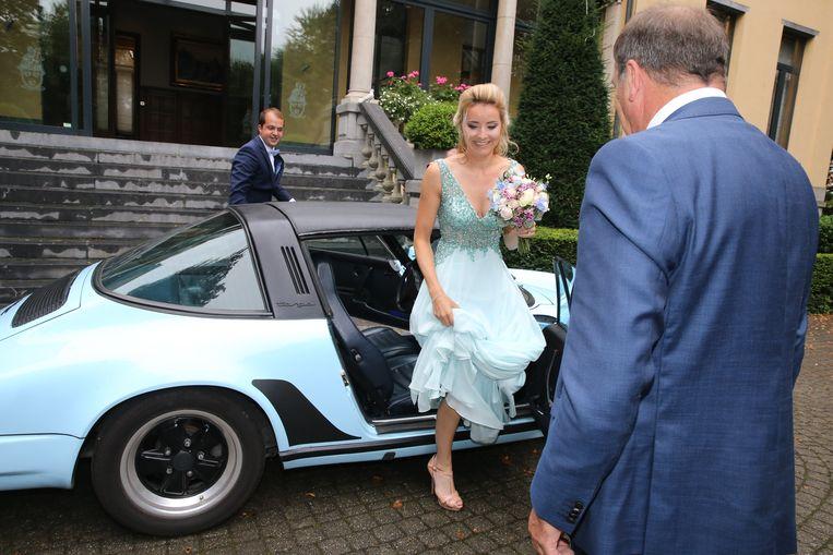 Charline stapt uit de Porsche aan het gemeentehuis. De kleur past perfect bij haar jurk.
