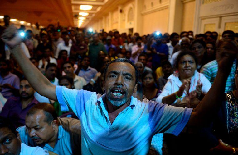 Supporters van de afgezette premier Ranil Wickremesinghe demonstreren voor de officiële residentie van de huidige premier Mahinda Rajapaksa in Colombo. Beeld AFP