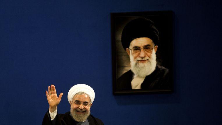 De president van Iran, Hassan Rouhani bij een portret van ayatollah Ali Khamenei. Beeld AFP