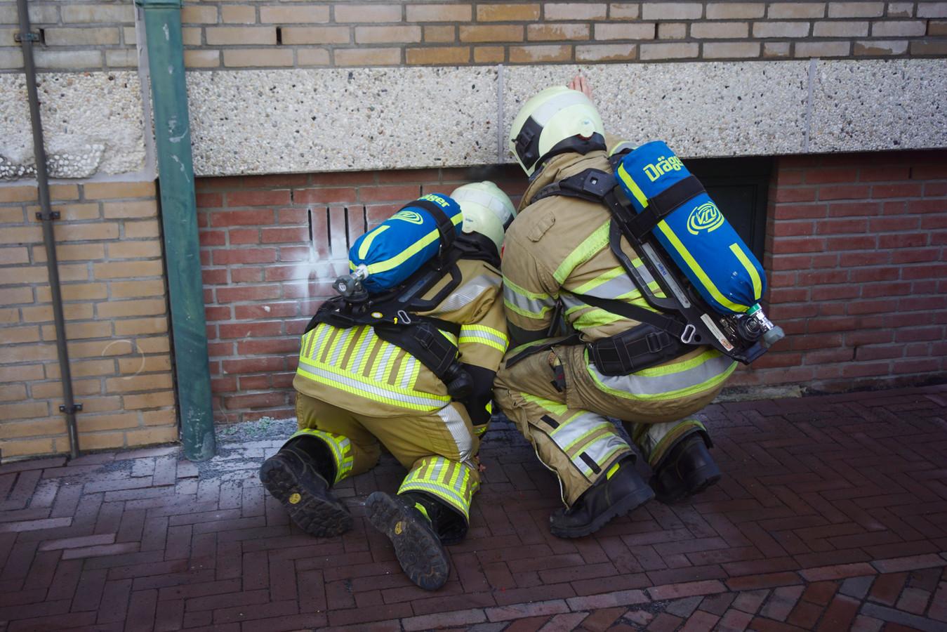 Brandweerlieden op 31 december in Bunschoten. Onverlaten stopten vuurwerk in een gat in een muur waarna brand ontstond.
