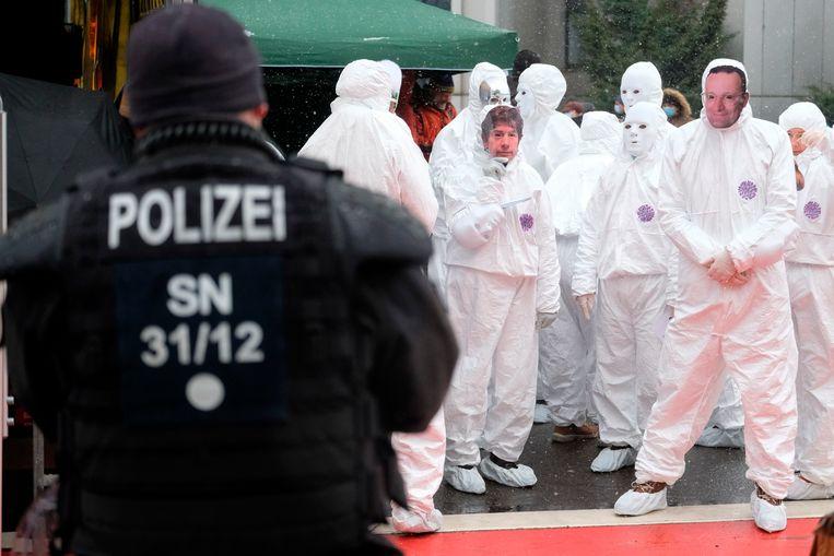 Demonstranten protesteren tegen het Duitse coronabeleid in beschermende pakken en maskers op met de beeltenis van viroloog Christian Drosten en Volksgezondheidsminister Spahn.  Beeld AP