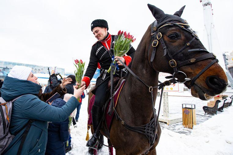 Een cadet van de rijschool van het Kremlin deelt bloemen uit aan een vrouw op vrouwendag. Beeld AP