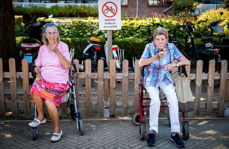 Ouderen van een zorgcentrum in het Rotterdamse Crooswijk genieten van een ijsje. Beeld ANP, Jerry Lampen