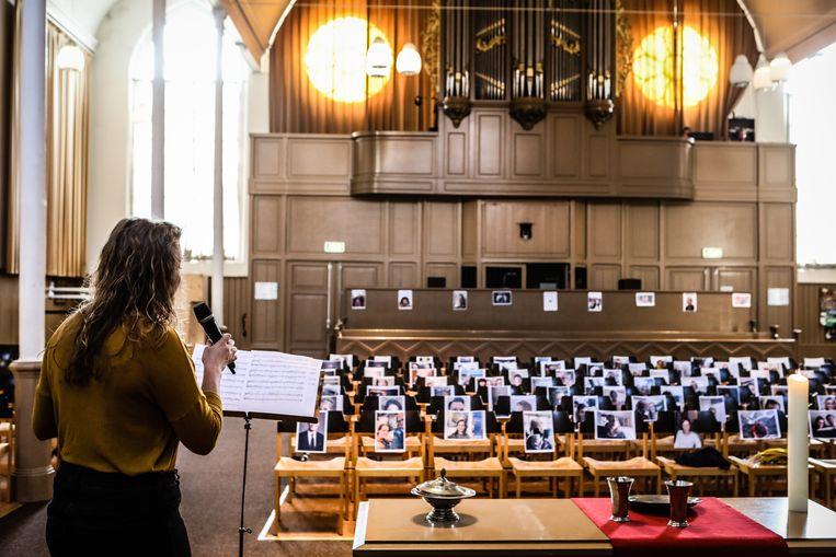 Een online kerkdienst vanuit de Herengrachtkerk in Leiden in een lege kerk vanwege de maatregelen rondom het coronavirus. Op de achtergrond hangen selfies van gemeenteleden op de stoelen. Beeld Hollandse Hoogte / Maarten Boersema