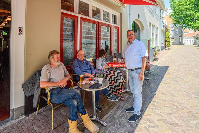 Ad van Oorschot (staand) runt café De Grote Slok met een terrasje van 6 bij 1 meter. Omdat hij zich niet altijd aan de vergunning zou houden, dreigt er een dwangsom van tien mille. 'Belachelijk', vindt stamgast Olivier Stroeks (links).