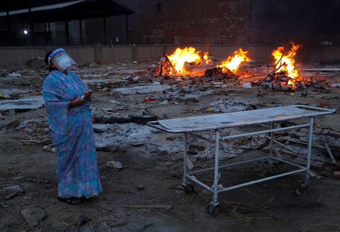 Een vrouw huilt bij de crematie van haar aan corona overleden echtgenoot in India.
