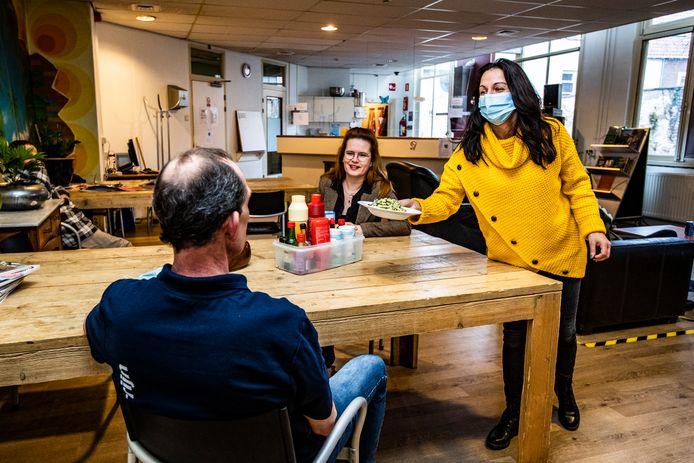 In de Deventer opvang voor verslaafden en daklozen geeft een vrijwilliger een bord eten.