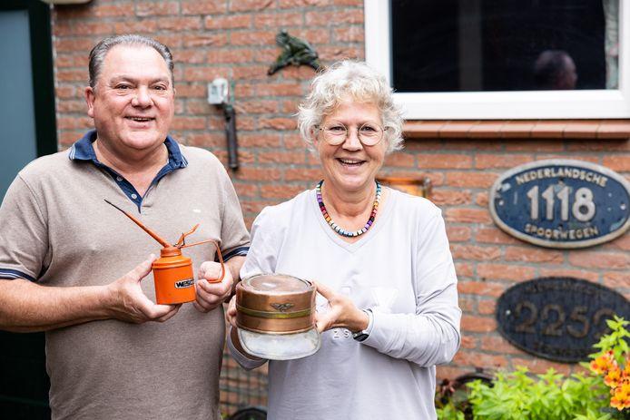 Joop Joosen en Monique Vos tonen twee bijzondere NS-attributen: een oud oliespuitje zoals de monteurs dat gebruikten en een  koperen conducteurspet, door collega's gemaakt voor een jubileum.