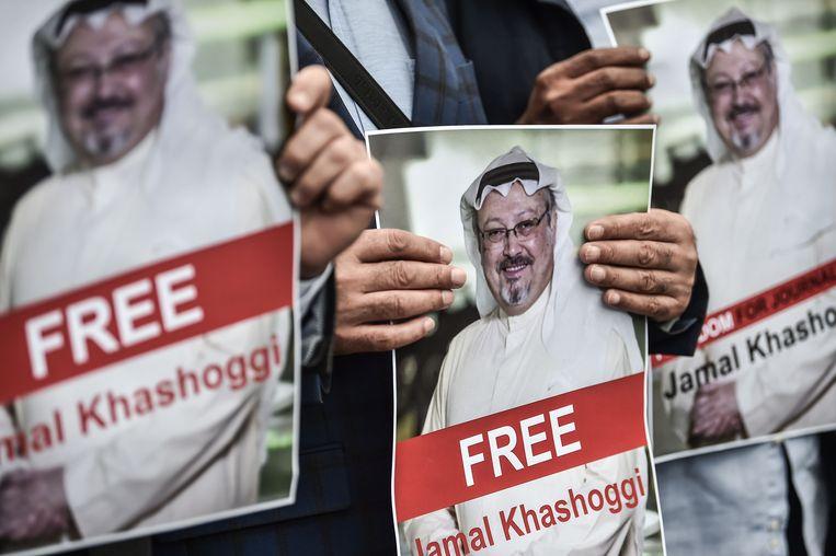 Demonstranten houden foto's van Jamal Khashoggi vast tijdens een demonstratie voor het Saoedi-Arabische consulaat in Istanbul. Beeld AFP