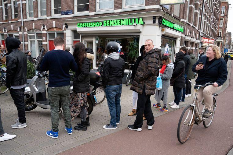 Drukte bij een coffeeshop waar klanten nog snel voor de lockdown een voorrraadje in willen slaan. Beeld ANP