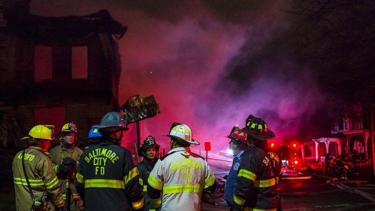 Brandweerlui blussen een woning in Baltimore. De stad staat onder hoogspanning, met rellen tussen jongeren en politie,, plunderingen en brandstichtingen. Beeld Adrees Latif / REUTERS