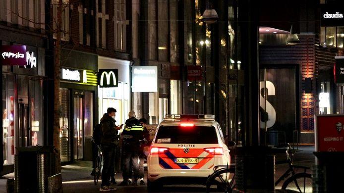 De politie controleert voetgangers in het centrum van Enschede na het ingaan van de avondklok.
