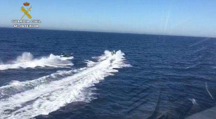 In volle achtervolging kwamen de twee boten met elkaar in botsing, waarbij drie agenten in zee belandden.