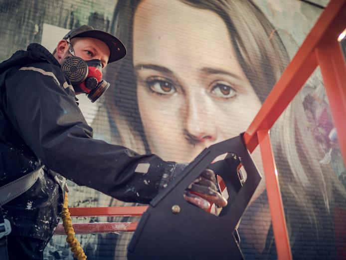 Kunstenaar Collin van der Sluijs zwoegde een week lang op het graffitiportret van Ellen Page in de Binckhorst.