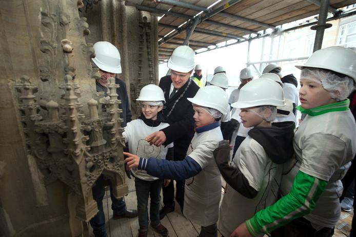 Schoolkinderen gaan met steenhouwers de Jacobstoren op. Die staat in de steigers voor restauratie, kinderen komen kijken (en gaan daarna naar de werkplaats) om het vak te leren kennen. Foto Theo Kock