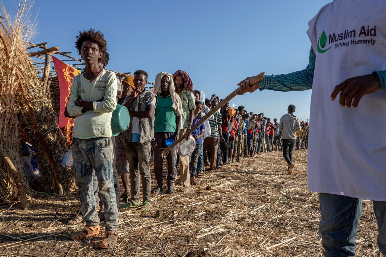 Vluchtelingen uit Tigray schuiven aan voor voedsel in het Om Rakouba-kamp net over de grens in Soedan. Beeld AP