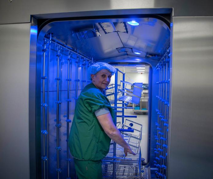 Miranda Bressers, hoofd van de afdeling centrale sterilisatie, toont de 'karrenwas', een wasmachine voor transportkarren.