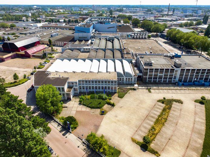 Beeld vanuit de lucht op het vijf hectare grootte terrein. Het voormalige hoofdkantoor, links op de voorgrond en een deel van de fabriekshallen met sheddaken daarachter blijven behouden.