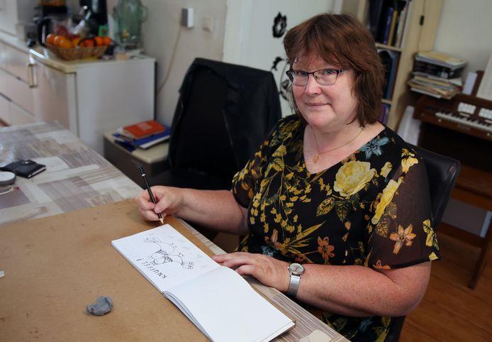 Trijntje Bos aan het werk in haar woonkamer in Rouveen.