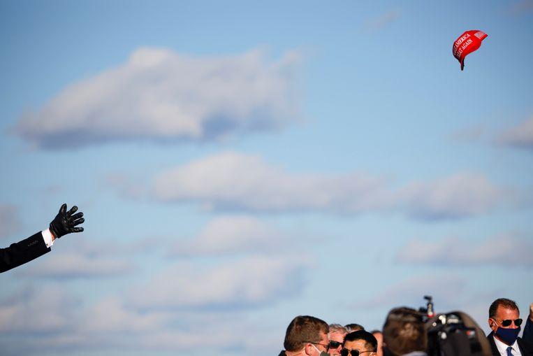 President Donald Trump gooit een pet met zijn slogan 'Make America Great Again' (MAGA) naar de bijeengekomen menigte. Beeld REUTERS