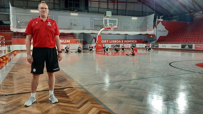 Coach Erik Braal in de basketbalhal van Benfica, terwijl zijn spelers op de achtergrond bezig zijn met een warming-up.