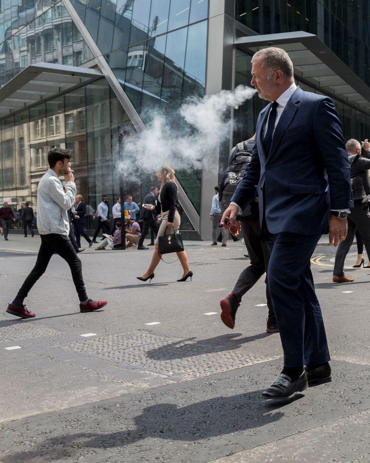 Een man in de Londense City lurkt aan zijn e-sigaret. 6 procent van de Britse bevolking vapet, dubbel zoveel als vijf jaar geleden. Beeld In Pictures via Getty Images