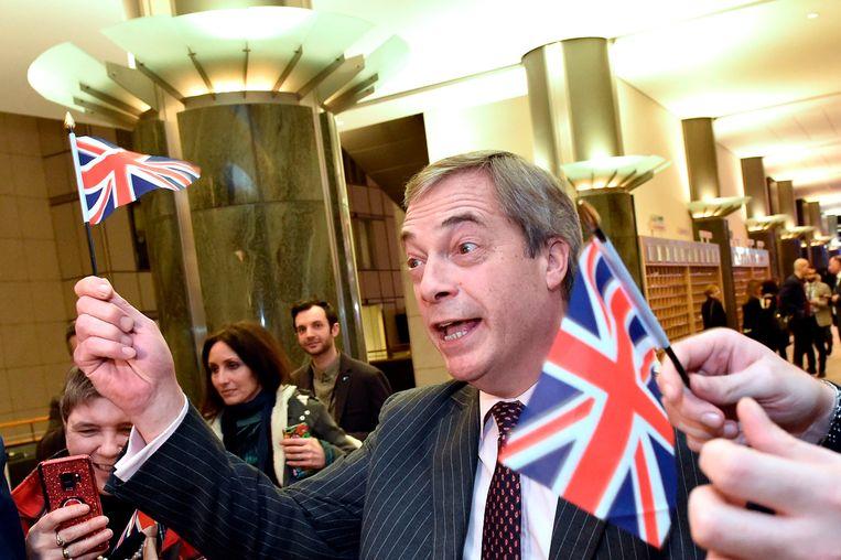 Nigel Farage zwaait met een Brits vlaggetje Beeld AFP