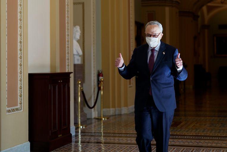 Chuck Schumer, de leider van de Democraten in de Senaat, steekt zijn duimen op nadat het steunpakket is aangenomen. Beeld AP