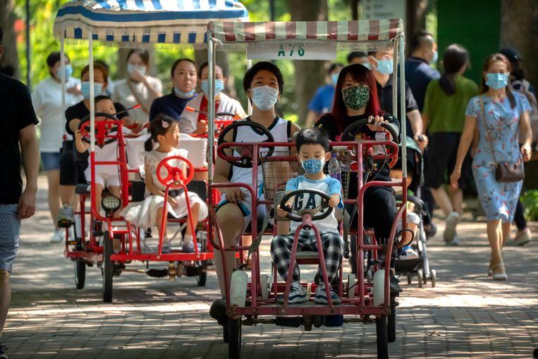 Ouders en hun kind(eren) maken een ritje door een park in Beijing. Beeld AP