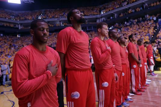 Spelers van de L.A. Clippers luisteren voor de wedstrijd tegen de Warriors naar het Amerikaanse volkslied, met hun warming-upshirts binnenstebuiten.