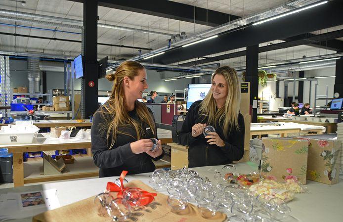 Lianne Quist en Cynthia Romer zijn kerstballen met een foto erin aan het maken op de afdeling Smallcraft.