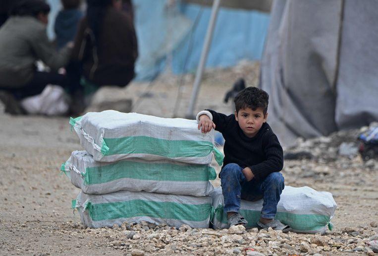 Een Syrisch jongetje zit naas hulpgoederen in een vluchtelingenkamp in het stadje Mehmediye aan de Syrisch-Turkse grens. Archiefbeeld. Beeld AFP