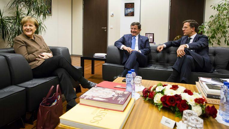 Mark Rutte en Angela Merkel hebben een ontmoeting met de Turkse premier Ahmet Davutoglu op de ambassade van Turkije. Beeld ANP