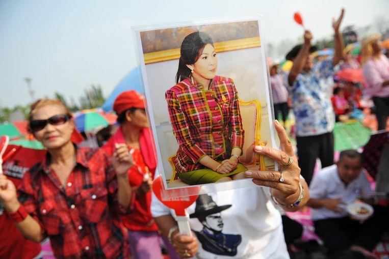 Een roodhemd (pro-regeringsdemonstrant) met een portret van premier Shinawatra in Ayutthaya Beeld getty