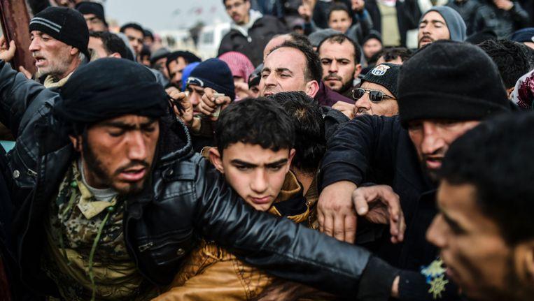 Vluchtelingen verdringen elkaar in een provisorisch vluchtelingenkamp nabij de stad Azaz. Beeld AFP