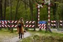 Een wandelaar met haar hond passeert de onbewaakte spoorwegovergang aan de Loorsteeg.
