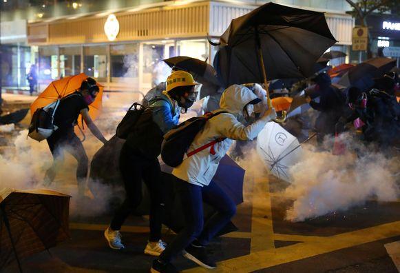 Demonstranten rennen in een wolk van traangas weg van de politie.
