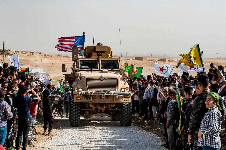 Koerden verzamelen zich afgelopen zondag tijdens een demonstratie in de Noord-Syrische stad Ras al-Ain rond een Amerikaans legervoertuig. Ze zijn bang dat het vertrek van Amerikaanse troepen voor Turkije het sein zal zijn voor een grondoffensief tegen de Koerden. Beeld Delil Souleiman / AFP