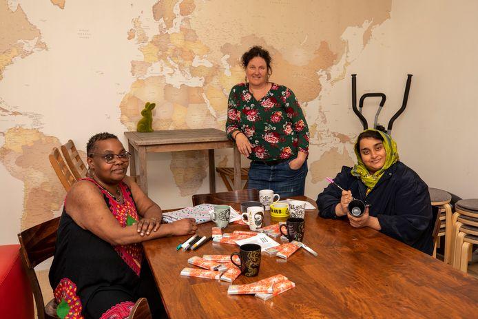 Milaijka (links) en Amira zijn vrijwilligers in de Kansenfabriek Schiedam en werken aan de pakketjes voor Schiedamse hulpverleners. Brenda Flapper (midden) coördineert het project.