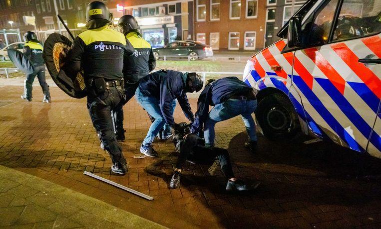 Een man wordt aangehouden na een confrontatie op de Beijerlandselaan waar de aanwezige politie werd bekogeld met stenen en vuurwerk.  Beeld ANP